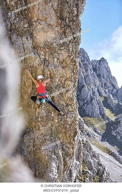Austria, Innsbruck, Nordkette, woman climbing in rock wall