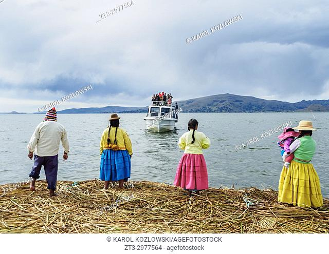 Native Uro Family waiting for the boat with tourists, Uros Floating Islands, Lake Titicaca, Puno Region, Peru