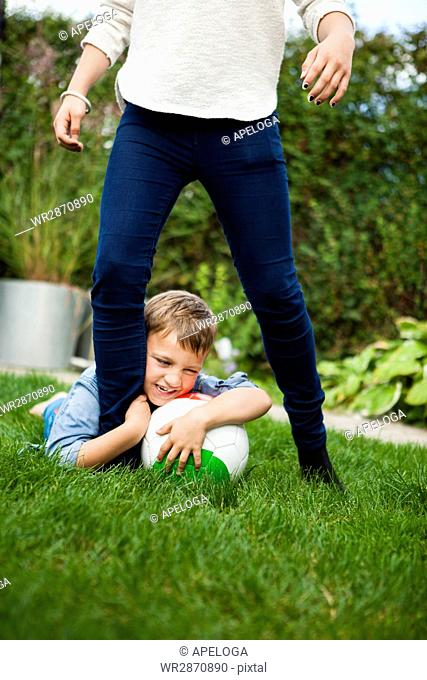 Cheerful boy playing with sister on grass at back yard