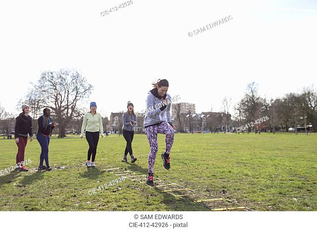 Focused woman doing speed ladder drill in sunny park