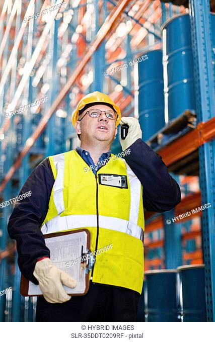 Worker using cell phone in warehouse