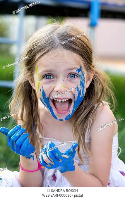 Germany, Bavaria, Portrait of girl playing with finger paint, smiling