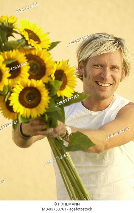 Man, holds cheerfully, sunflowers,,  Portrait  Men's portrait, man, young, blond, Shirt, T-shirt, summery, flowers, Helianthus annuus, flower bouquet, gives