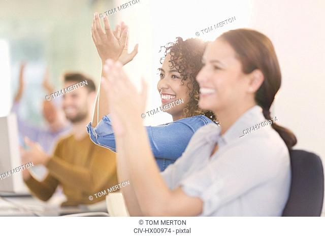 Businesswomen smiling and clapping in meeting