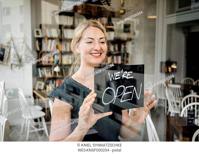 Smiling woman in a cafe attaching open sign to glass pane