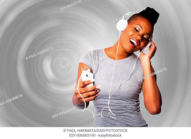 Beautiful young woman with headphones and mobile device listening grooving singing to music, gray circular background