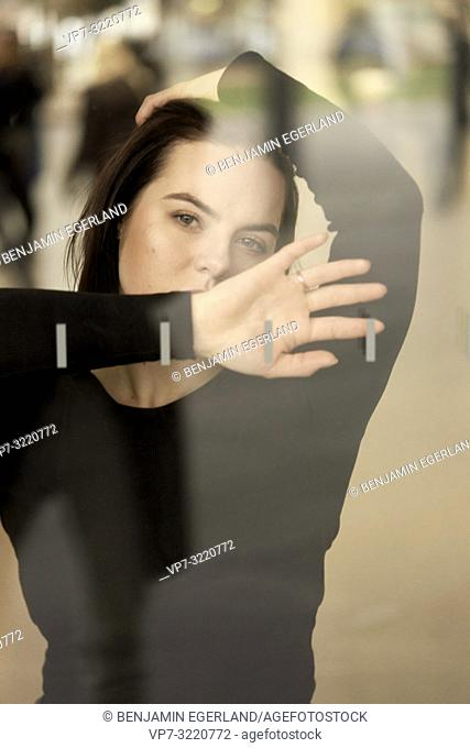 portrait of a woman indoors behind glass window, playful sensual emotion, in Munich, Germany