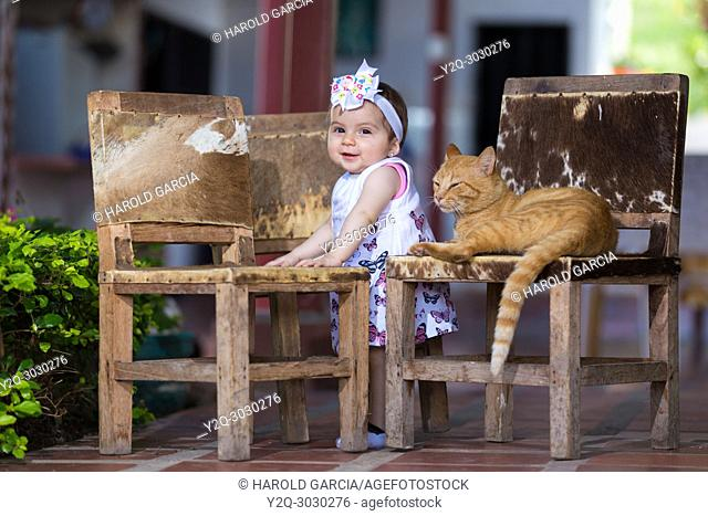 Baby girl standing next to chairs playing with a cat