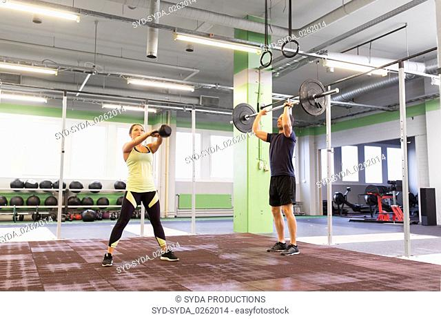man and woman with weights exercising in gym