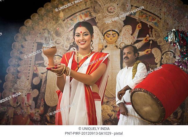 Bengali woman performing Dhunachi Dance and a Dhaki playing Dhak at Durga Puja