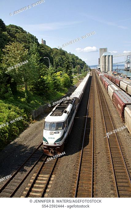 An Amtrak Talgo passenger train just west of downtown Tacoma, Washington, USA and headed north toward Seattle. Commencement Bay is visible in the background