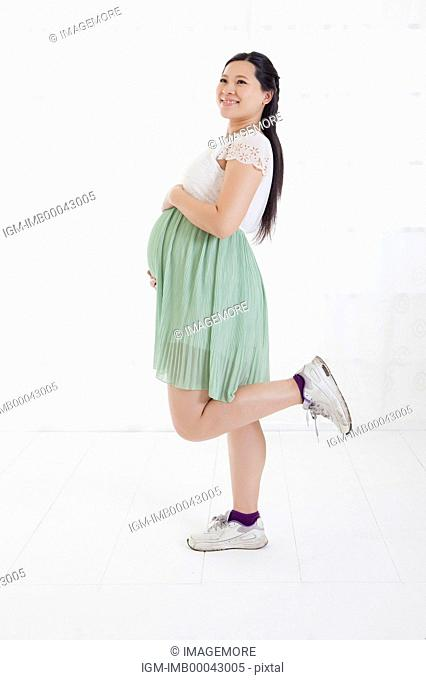 Pregnant woman standing with one leg and looking up with smile