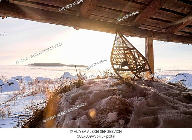 Pair of snow shoes in barn with distant snow covered fields, Ural, Russia