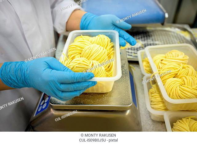 Worker weighing portions of tagliatelle in pasta factory, close up