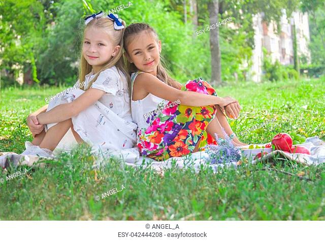 Two smiling girls sitting back-to-back on green grass in the park in summer