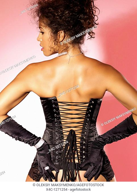 Beautiful woman wearing a black corset and gloves