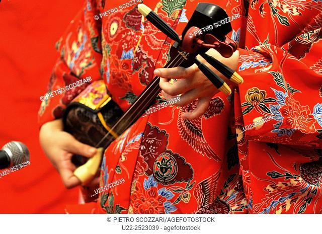Naha, Okinawa, Japan: a woman wearing a traditional Bingata dress playing sanshin at Sakaemachi Market