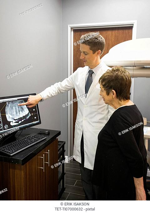 Dentist showing patient x-ray on computer screen