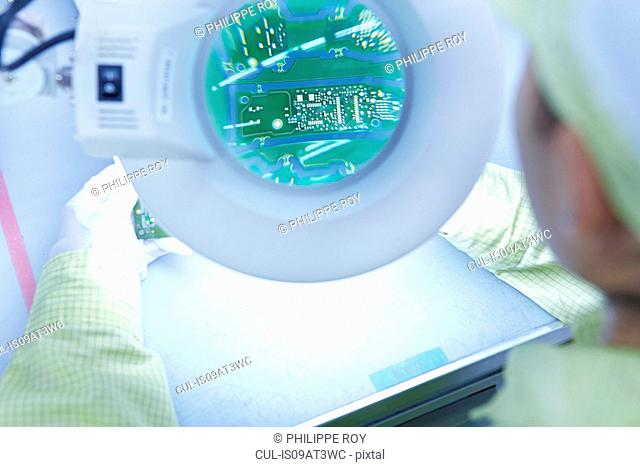 Young woman using magnifier at quality check station at factory producing flexible electronic circuit boards. Plant is located in the south of China, in Zhuhai