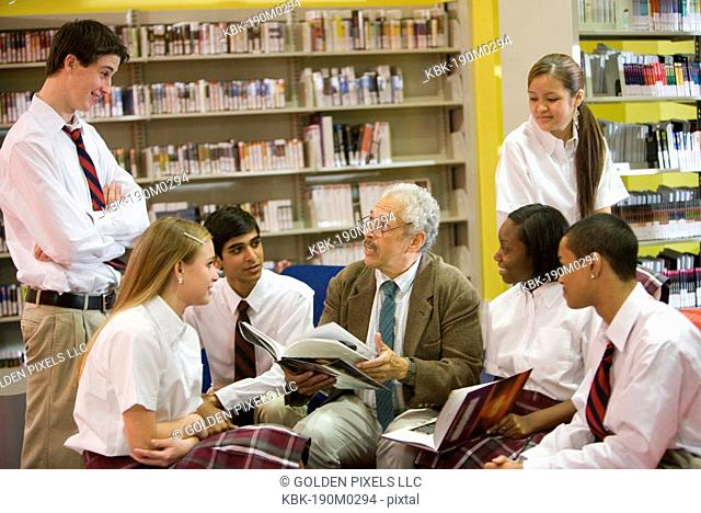 Group of high school students reading in library with teacher