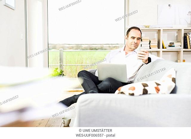 Businessman on couch using laptop and cell phone