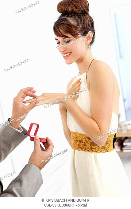 Man putting engagement ring on fiance