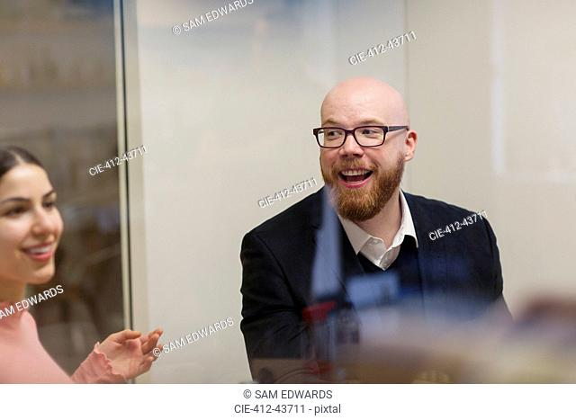 Smiling businessman listening to colleague in office