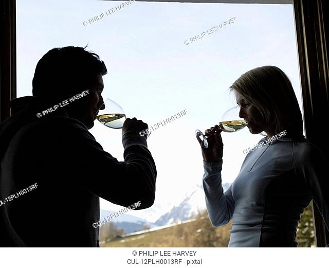 woman and man at window drinking