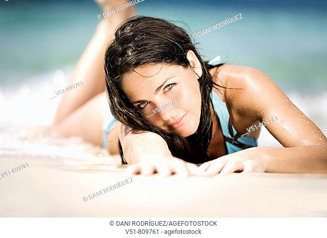 Woman laying in the sand by the sea