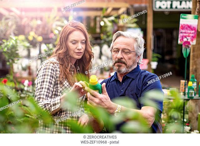Gardener helping woman at garden centre