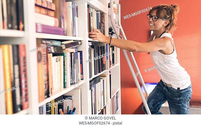 Woman taking a book from bookshelf