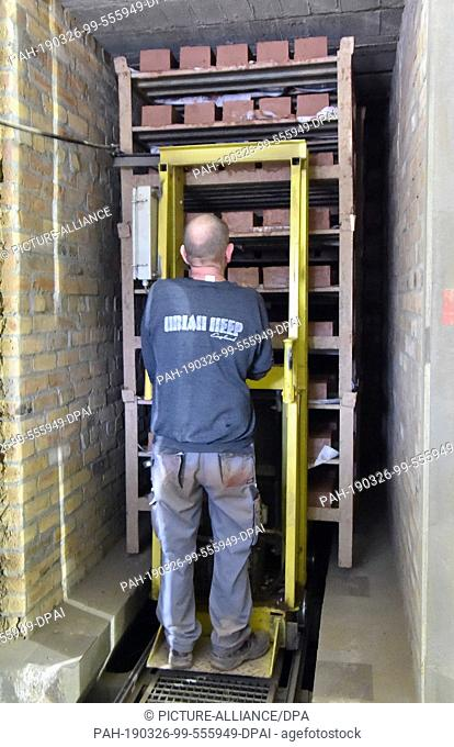 26 March 2019, Brandenburg, Glindow: An employee of the brick factory pushes a pallet of bricks into a drying chamber. The company with 20 employees produces...