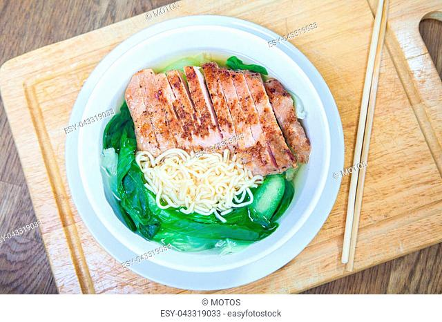 Instant Noodles with fried Pork Cutlet with Pak Choy or Chinese Cabbage in white bowl and Plate on wooden table