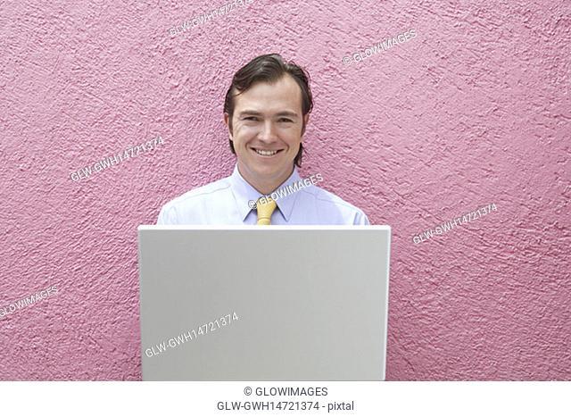 Portrait of a businessman holding a laptop