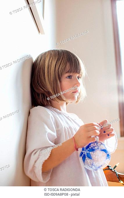 Child with blue bauble day dreaming
