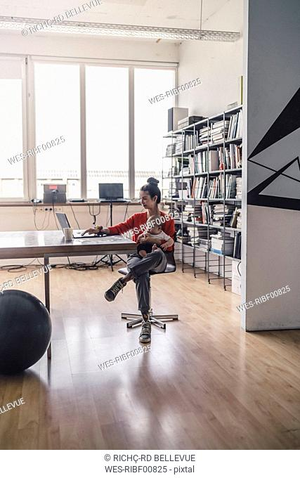 Working mother with baby on her lap, sitting in office, using laptop