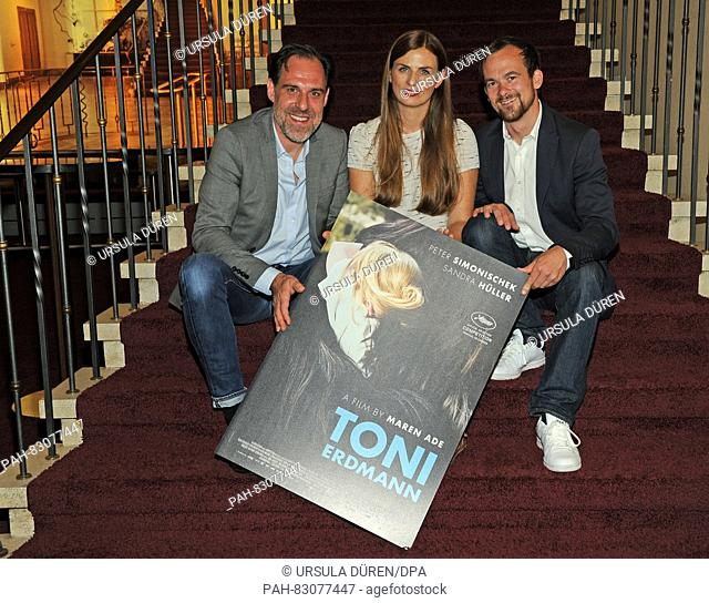 Actor Thomasd Loibl (l-r) and producers Janine Jackowski and Thomas Dornbach posing with the Toni Erdmann poster at the Gloria Palast in Munich, Germany