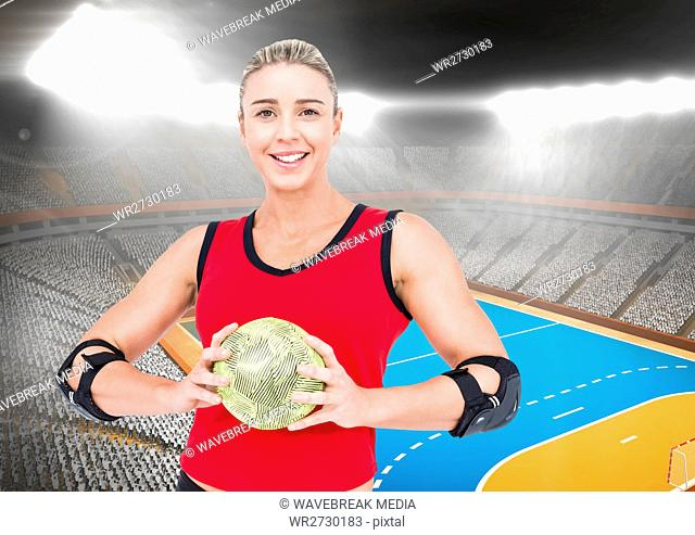 Portrait of happy female handball player holding ball with stadium in background