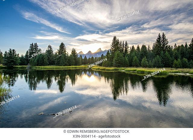Sunlight creeps behind peaks of Teton Mountain Range with glassy water in the foreground, Grand Tetons National Park, Teton County, Wyoming. USA