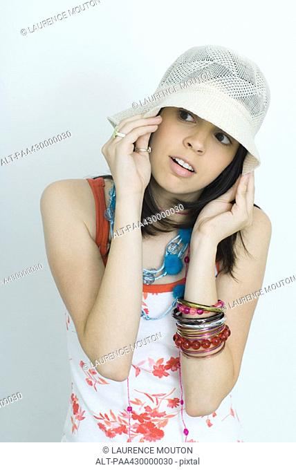 Teenage girl pulling down hat, looking to the side, portrait