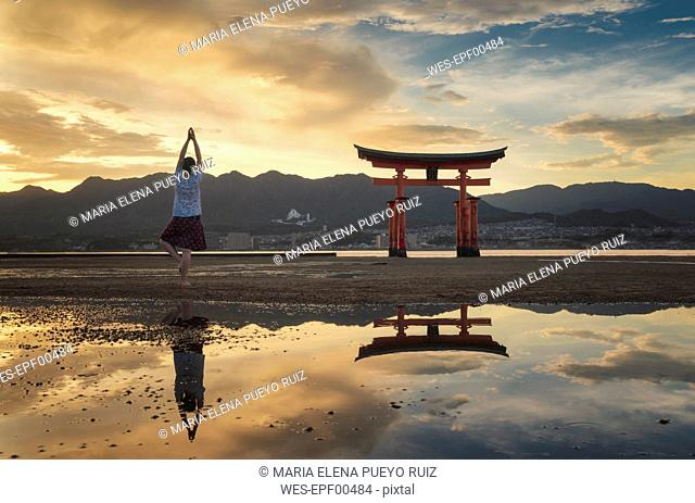 Woman enjoying the sunset on Itsukushima Island or Miyajima, Hiroshima, Japan