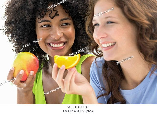 Close-up of two smiling female friends eating fruits