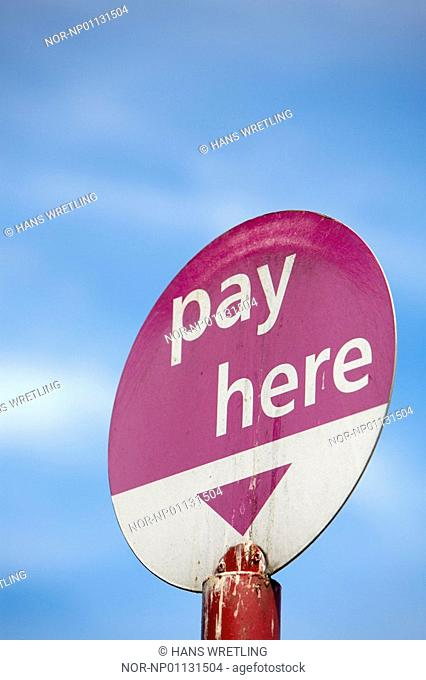 Low angle view of a Pay Here signboard, England