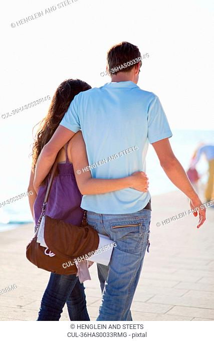 Couple walking and hugging on beach