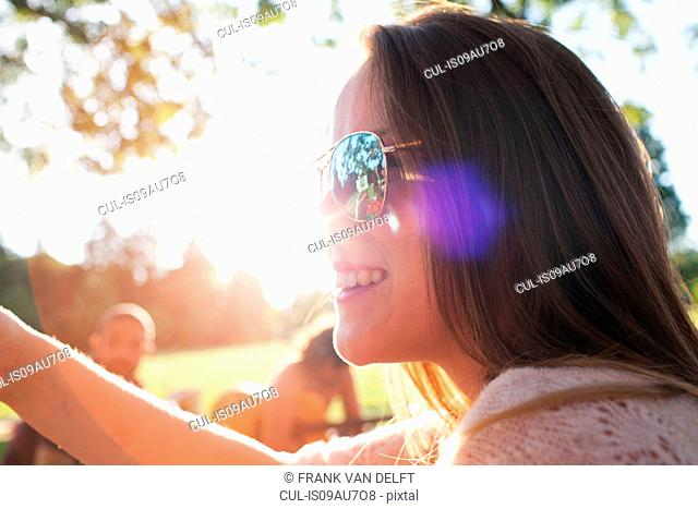 Close up of happy young woman at sunset park party