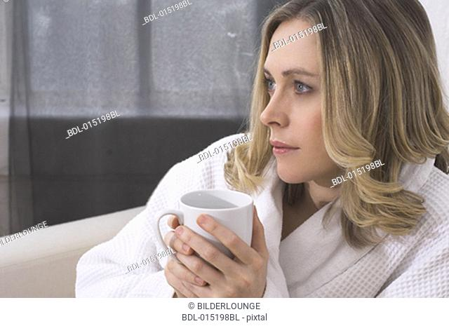 portrait of thoughtful young woman in bathrobe holding mug