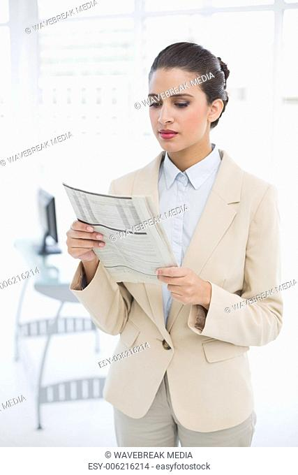 Attentive smart brown haired businesswoman reading a newspaper