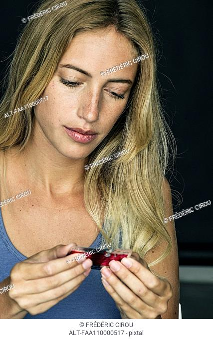 Woman reading information on vial