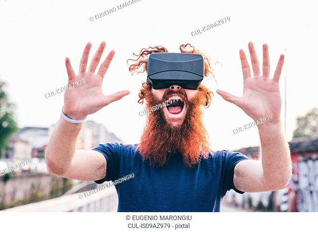 Portrait of young male hipster with red hair and beard screaming whilst wearing virtual reality headset