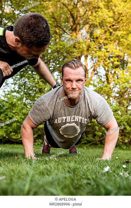 Man motivating friend doing push-ups at park